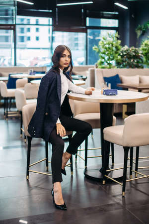 Beautiful young woman drinks coffee in cafe before important working meeting