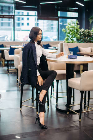 Pretty young lady in classic clothes in a restaurant