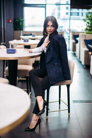 Cute brunette spending time in a cafe and enjoy hot drink