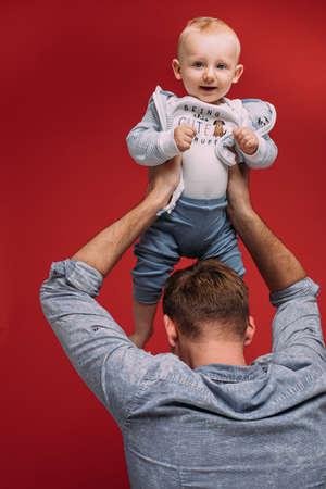 Studio portrait of cute boy in fathers arms. Zdjęcie Seryjne