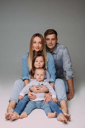 Family of four posing in denim dress code