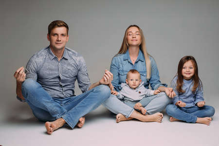 happy family meditate together in the studio