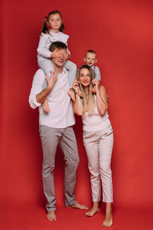 Parents with children in studio on red background.
