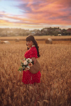 Picture of a beautiful young woman walking on a large field in the evening with flowers Zdjęcie Seryjne
