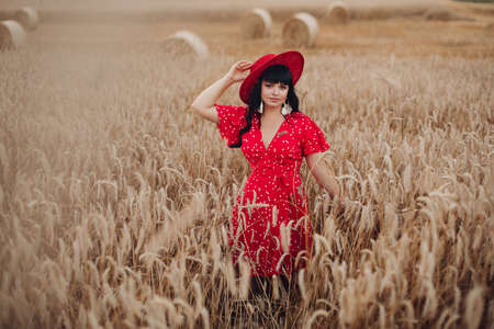Picture of a beautiful young woman walking on a large field and enjoys