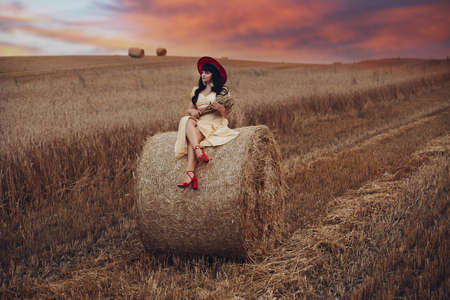 Beautfiul young woman sits on the big haystack on the field