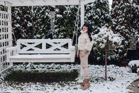 Pretty brunette young female wearing warm winter clothes standing near garden swing outdoor in wintertime