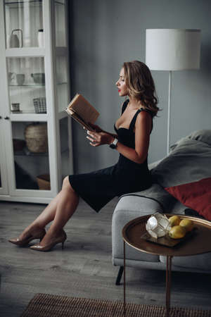 clever and beautiful woman reading a book after hard working day