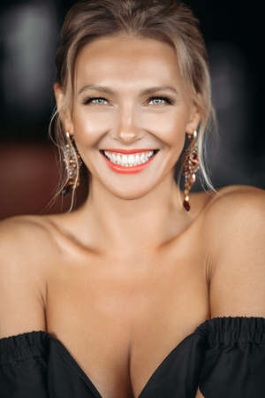 Portait of cheerful caucasian lady smiles, picture isolated on dark blur background