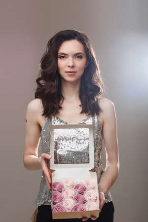 Slender model with gift. Copy space. Isolated on grey background.