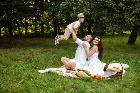 Family having fun at picnic in the park or forest at picnic on the grass. Zdjęcie Seryjne