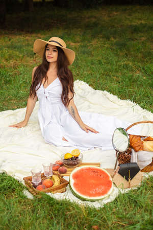 Portrait of a young beautiful girl with even white teeth, a beautiful smile in a straw hat and long white dress have a picnic in the garden