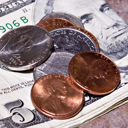 dime: Coins laying on a five dollar bill ( quarter, nickel, dime, penny )