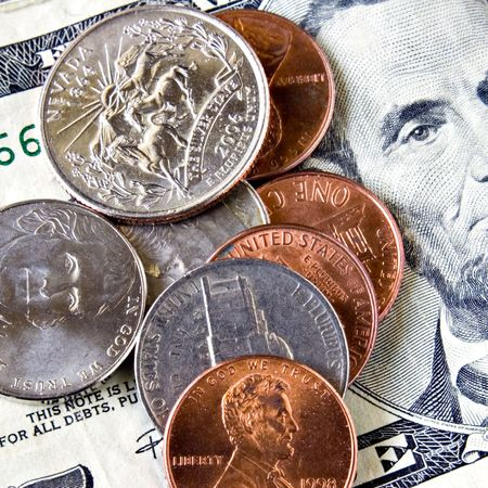 Coins laying on a five dollar bill ( quarter, nickel, dime, penny ) Stock Photo - 792971