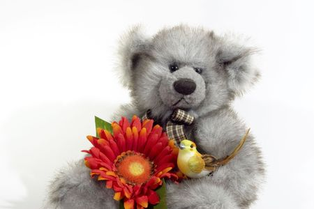 Teddybeer met oranje bloemen en gele vogel Stockfoto