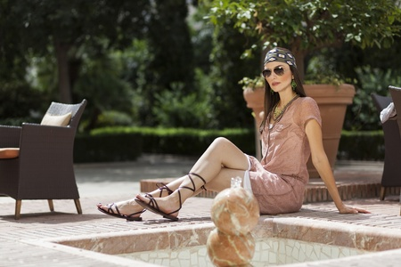 Woman posing with sunglasses and bandana in a fountain photo