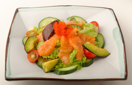 Raw salmon and avocado salad on a square plate.