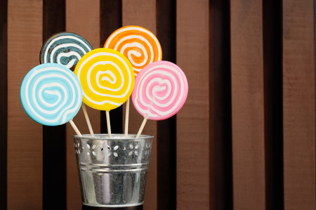 Five lollipops stacked in a metal pot with brown wood planks behind. Lollipops are yellow, pink, blue, orange and dark purple with white swirls. Copy space to the right.