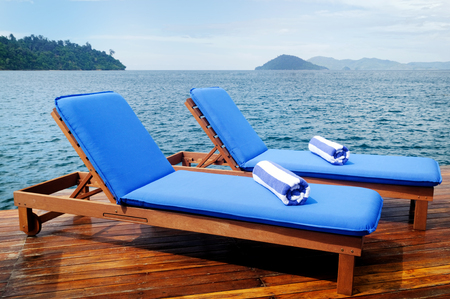Pair of outdoor reclining seats on deck near large lake with hills in the distance. Matching blue and white towels in rolls on top.