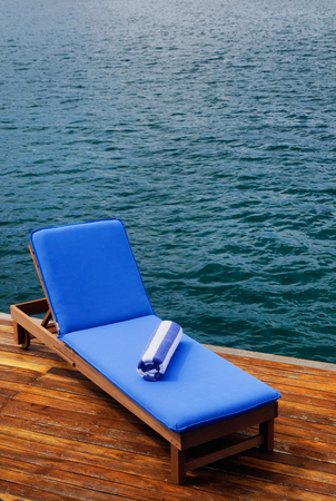 Outdoor reclining seat on deck next to lake. Matching blue and white towel rolled up on top. Zdjęcie Seryjne - 64826620