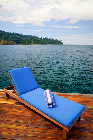 Outdoor reclining seat on deck next to lake. Matching blue and white towel rolled up on top.