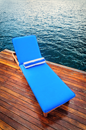 Outdoor reclining seat on deck next to lake. Matching blue and white towel rolled up on top. Zdjęcie Seryjne - 64826629