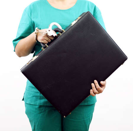 medical  pinned to kept black, leather suitcase with handcuffs woman in green uniform Stock Photo - 5923535