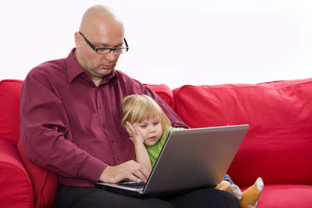 Father and daughter sitting on the red sofa at home and looking into a portable computer Stock Photo - 5918205