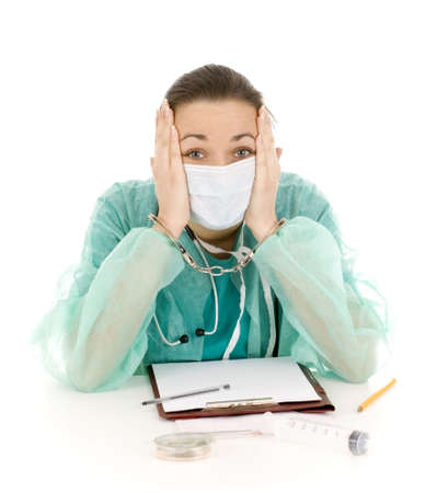 frightened  lady doctor in green uniform and medical mask with handcuffed hands at office Stock Photo - 6498142