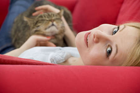 lying on red sofa young woman with cat