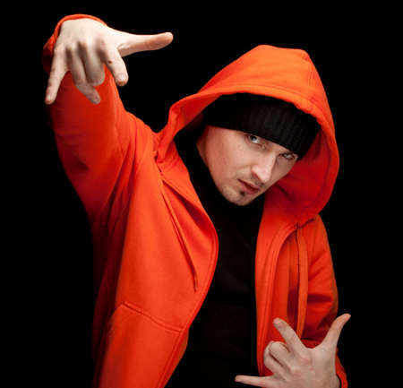 standing young man in orange sweatshirtand black cap, with raised arm, black background Stock Photo - 9036771
