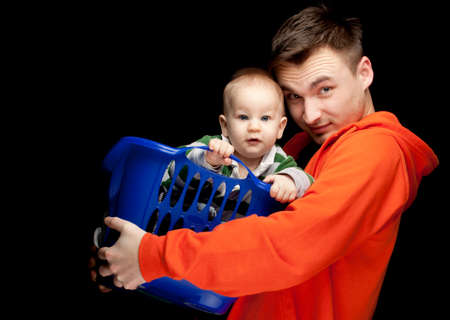portrait of young father holding its lovely six months old son, black background Stock Photo - 9080186