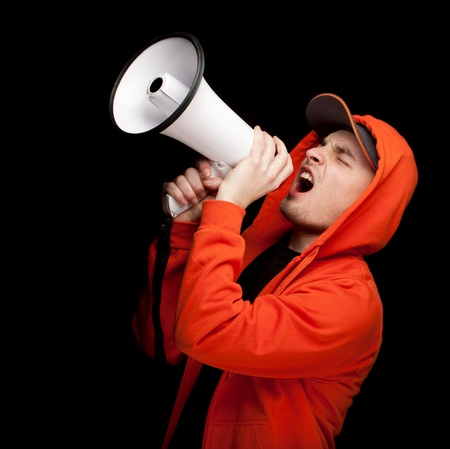 screaming young man in orange sweatshirt with megaphone, black background Stock Photo - 9401040