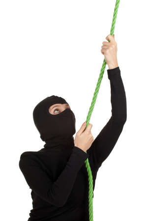 female thief in black clothes and balaclava climbing on green rope