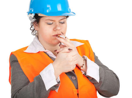 fat female architect or engineer in orange protective waistcoat and blue helmet  preparing to smoking cigarette, series Stock Photo - 10421156