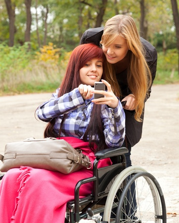 invalid girl on the wheelchair with mobie phone and friend outdoors photo