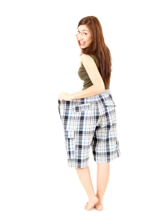 surprised weight lost woman in too big pants, white background Stock Photo - 15316796