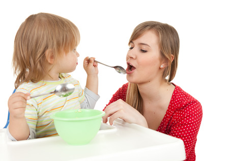 baby boy trying feed young mother, white background photo