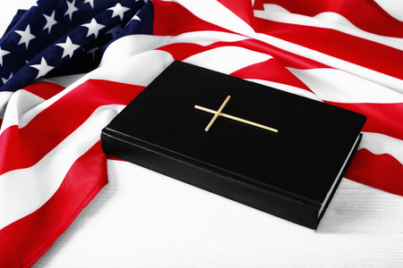 Holy Bible and American flag on a light wooden background. Black book with a cross and symbol of America. Religion of the American people. Independence Day as a religious holiday