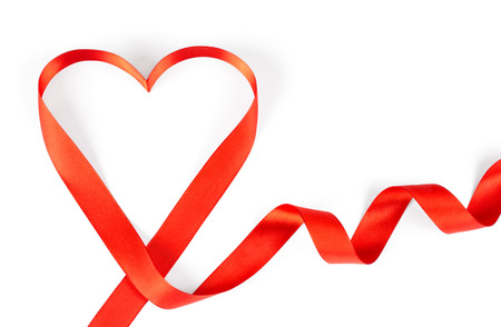 Red ribbon in the shape of heart on a white background with place for text. Greeting card, template for St.Valentine's day. Red heart on isolation with copy space.