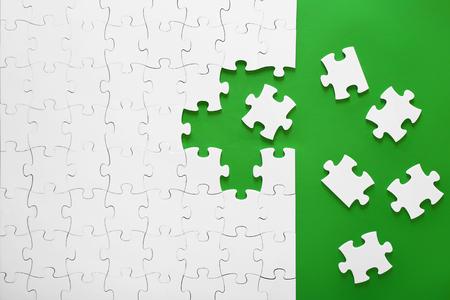 Rompecabezas blancos sobre un fondo verde. Las piezas del rompecabezas están juntas. El encabezado, la plantilla de una idea de negocio. Trabajo en equipo en la organización.