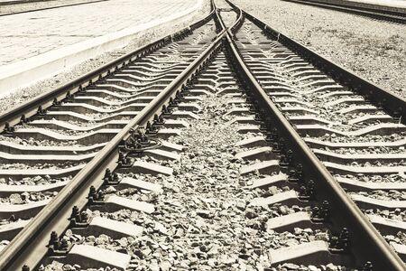 Die Konvergenz zweier Schienenwege als Symbol der unvermeidlichen Einheit des Lebens. Bahngleise mit Bahnsteig. Standard-Bild