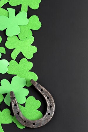 Template, preparation for St. Patricks Day. Clover and horseshoe on a dark background with place for text. Symbols of luck and fortune on isolation with copy space. Trefoil and rusty horseshoe top view. Stok Fotoğraf