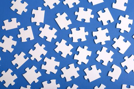 Scattered puzzles on a blue background. Many individual pieces of puzzles top view. Conceptual idea of teamwork to achieve the goal.