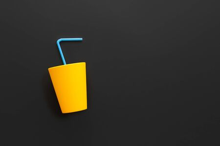Plastic pollutes the environment. A symbol of protecting nature from the threat of pollution. Plastic glass with a straw on a dark background as a sign of nature protection.