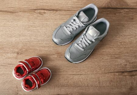Children and adult shoes on a wooden background top view. Conceptual imaginative vision of parenting. Small and large sneakers opposite each other.