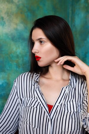 Serious pensive mystical portrait of a girl with red lips on an emerald background Фото со стока