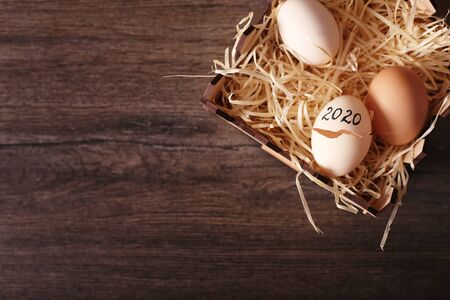 eggs with the inscription 2020 in a basket on a dark wooden background top view. The old year is leaving, a new one is breaking through.