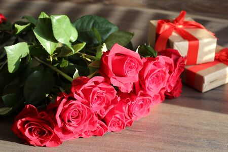 Bouquet of flowers and gift on a background.  Surprise from a beloved. St. Valentine present in the form of a bouquet of flowers, present idea