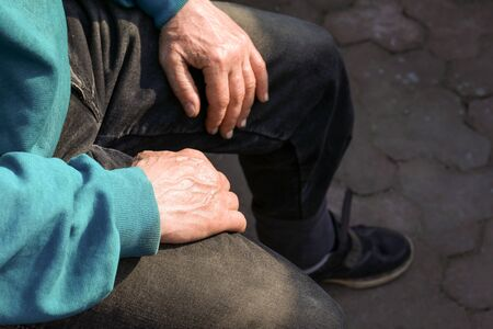 Close up old man hands with stick. Wrinkled hands of old man sitting alone outdoors and rests on a cane.